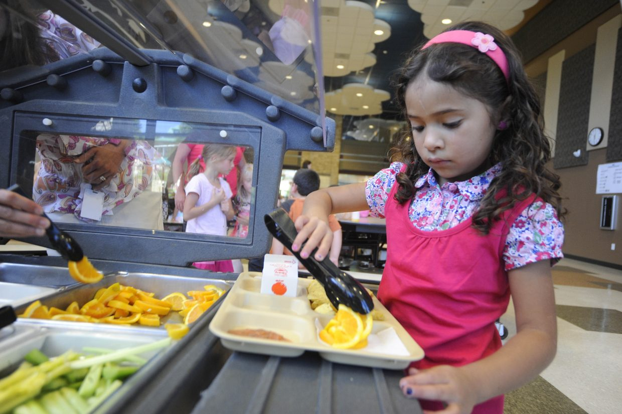 Soda Creek Elementary School second-grader Ximena Escarcega-Cano loads up her lunch tray with oranges at lunch during the first day of school Wednesday.