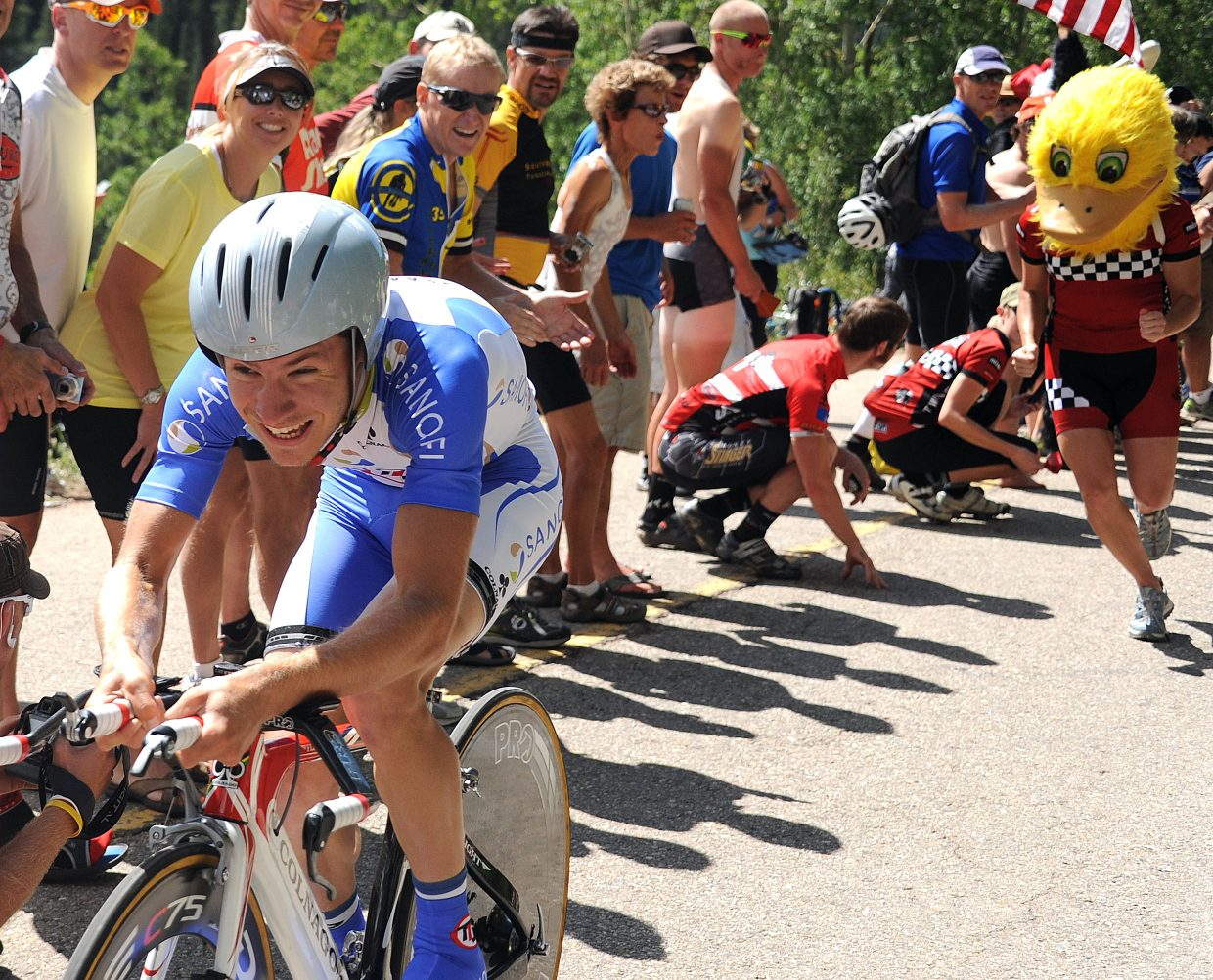 A woman in a duck head gives chase to a racer Thursday in the USA Pro Cycling Challenge in Vail. Spectators lined the streets during Stage 3 of the inaugural event.