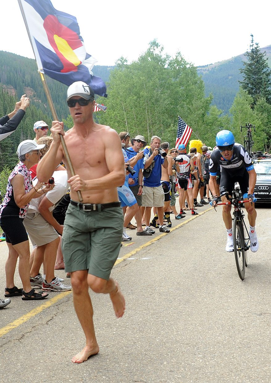 A Colorado-flag toting fan leads American cyclist Christian Vande Velde toward the finish line Thursday in Vail during the third stage of the USA Pro Cycling Challenge.