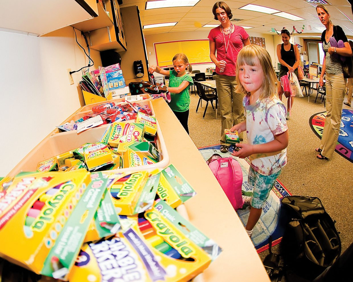 Kindergartners Kaela Pedersen, front, and Ava Rose drop off school supplies and meet their new teacher Hadley Nylen on Wednesday. The young students will begin their school year today.