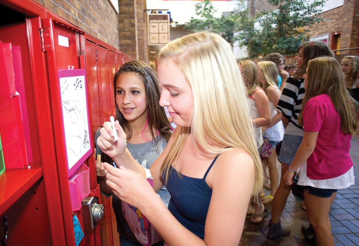 Middle school student Reina Salky looks over classmates Kristen Kinzie's shoulder as she leaves a message in her locker on the first day of classes at Steamboat Springs Middle School on Wednesday.