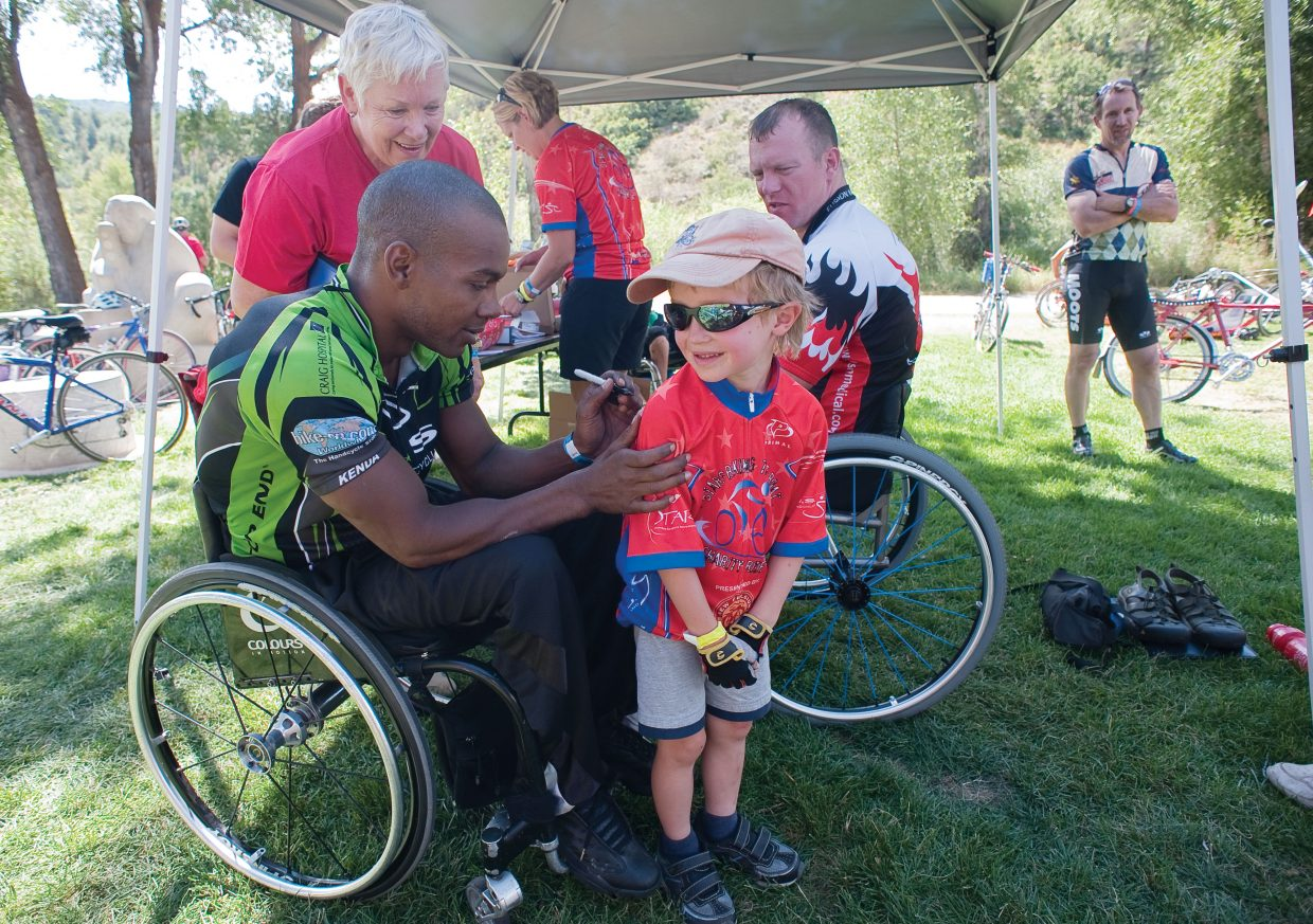 Paracyclist Delmon Dunston signs an autograph on the back of six-year-old Sal Malone's jersey at Saturday's STARS charity ride party in Little Toots Park. Dunston had raced in Friday's events and was on hard for Saturday's charity event before heading back to his home in California.