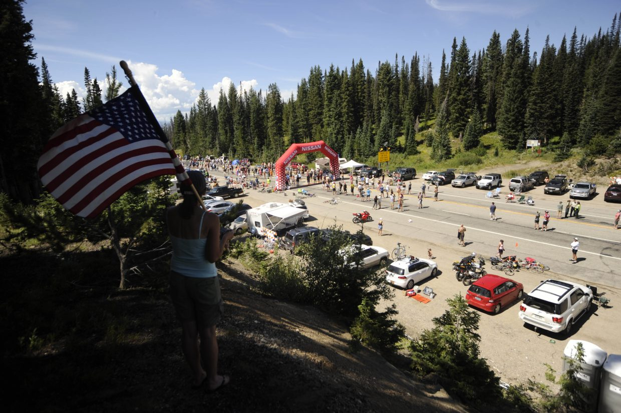 Steamboat Springs resident Cindy Ptach waits for the riders to arrive at the Rabbit Ears Pass west summit Saturday during the USA Pro Cycling Challenge.