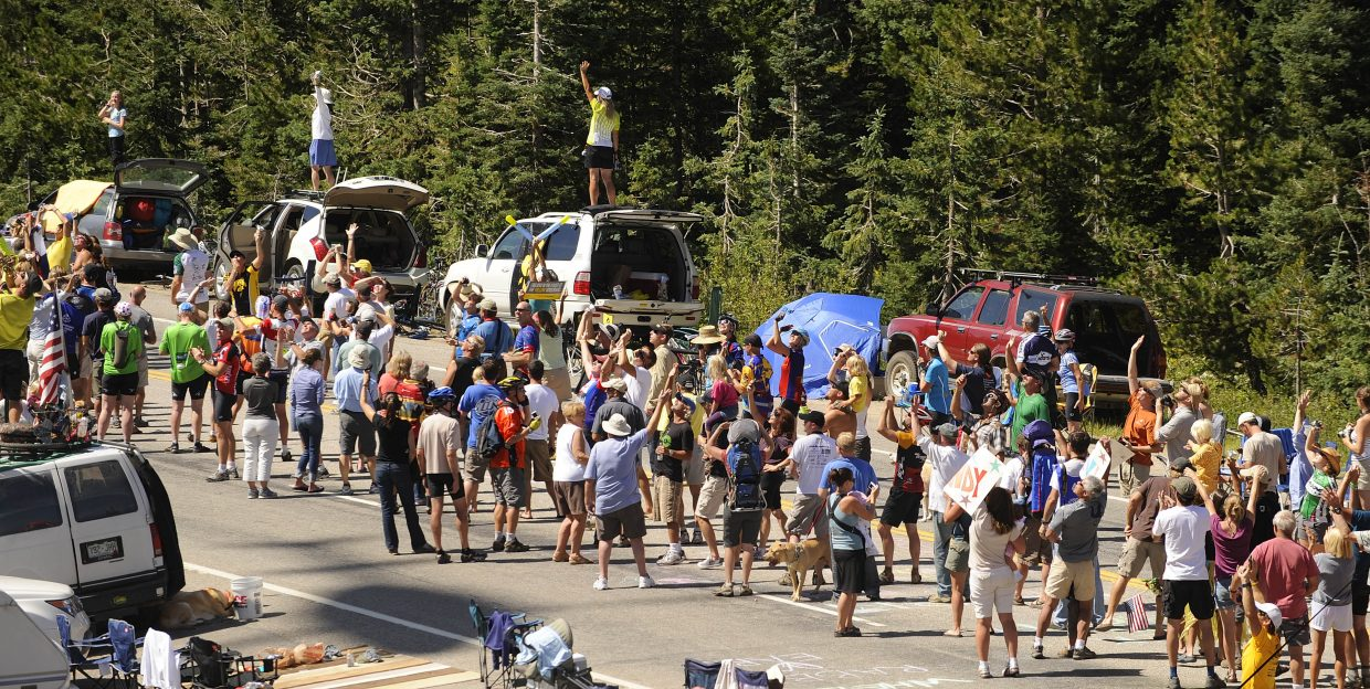 Spectators look up at a helicopter Saturday during the USA Pro Cycling Tour.