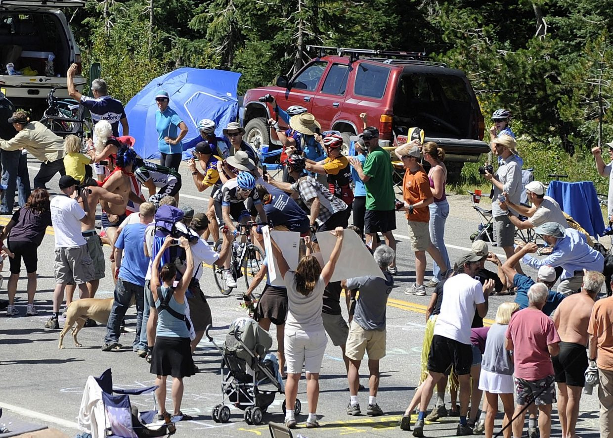 Spectators surround a rider at the Rabbit Ears Pass west summit on Saturday during the USA Pro Cycling Tour.
