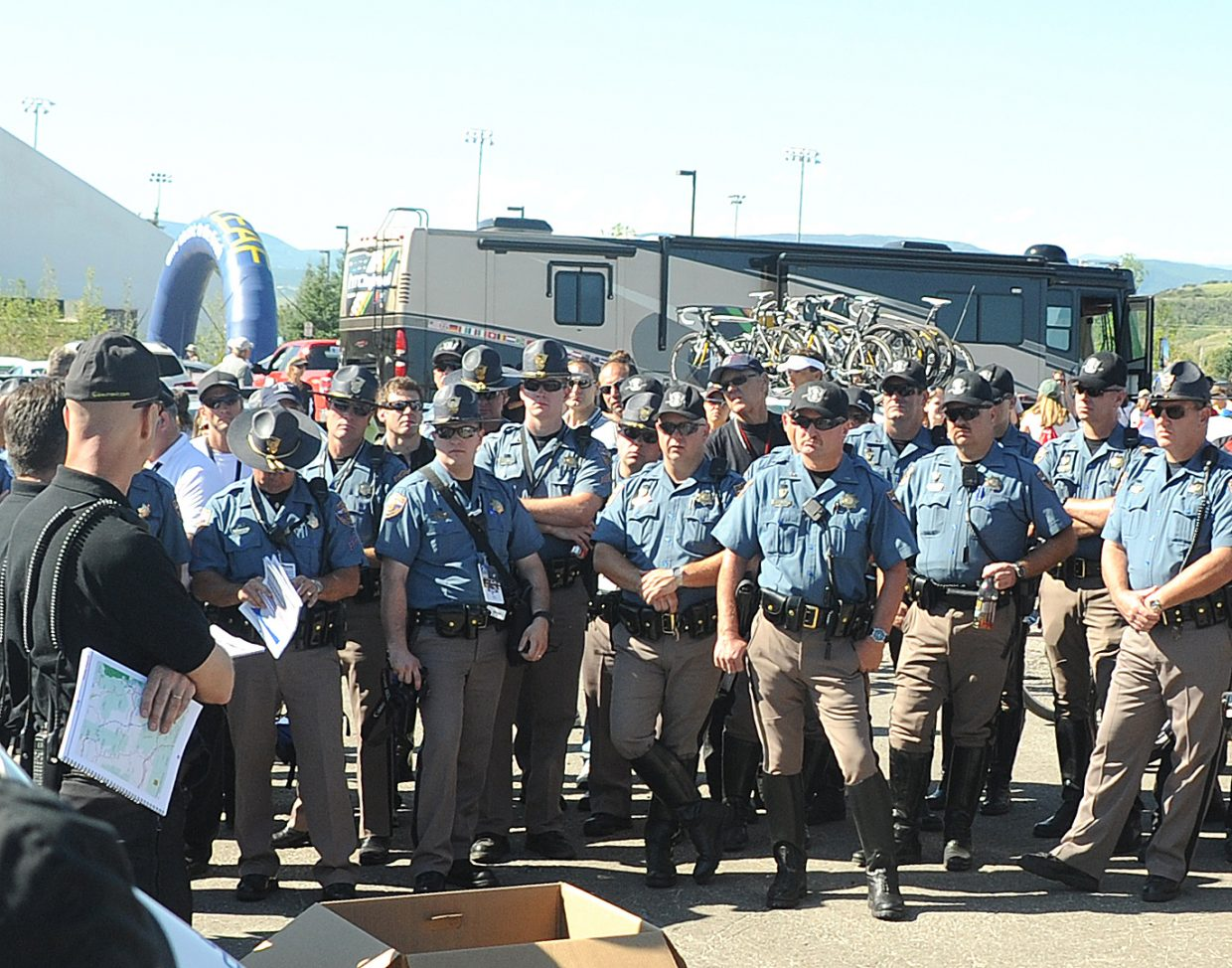 Colorado State Patrolmen get instruction before the start of Stage 5 of the USA Pro Cycling Challenge on Saturday.