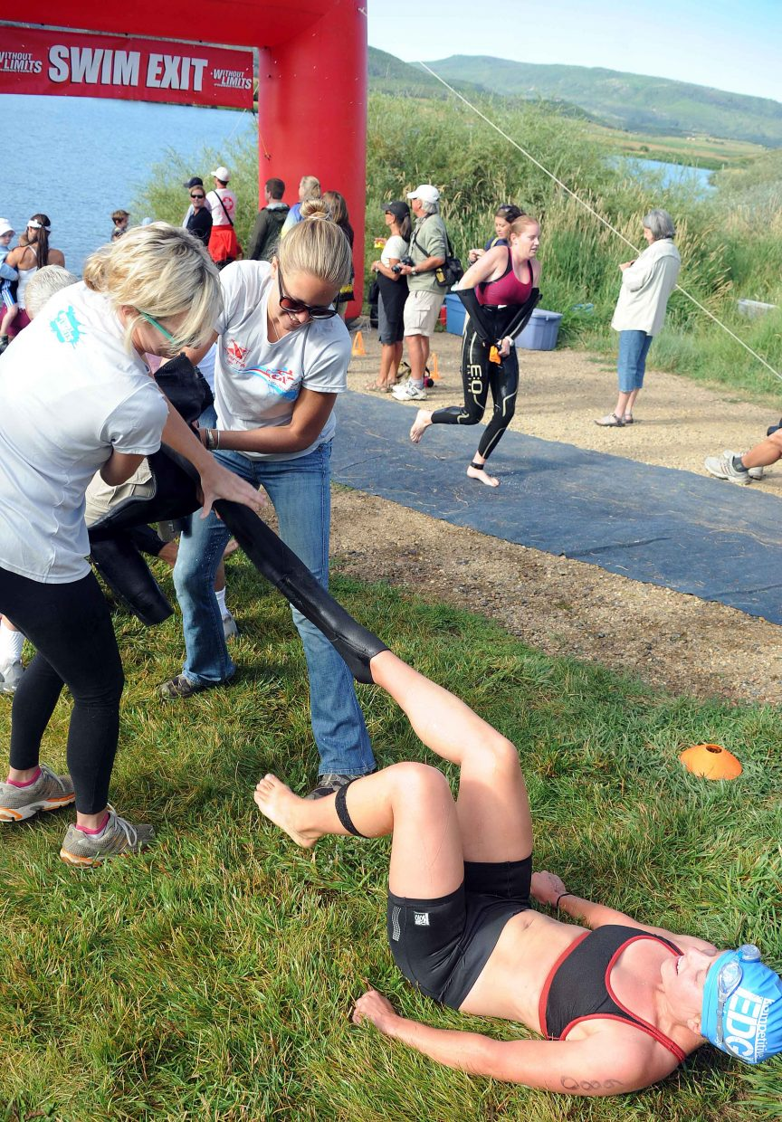 Volunteers rip Abby Johnson's wet suit off her Sunday as she left the water during the Steamboat Springs Triathlon.