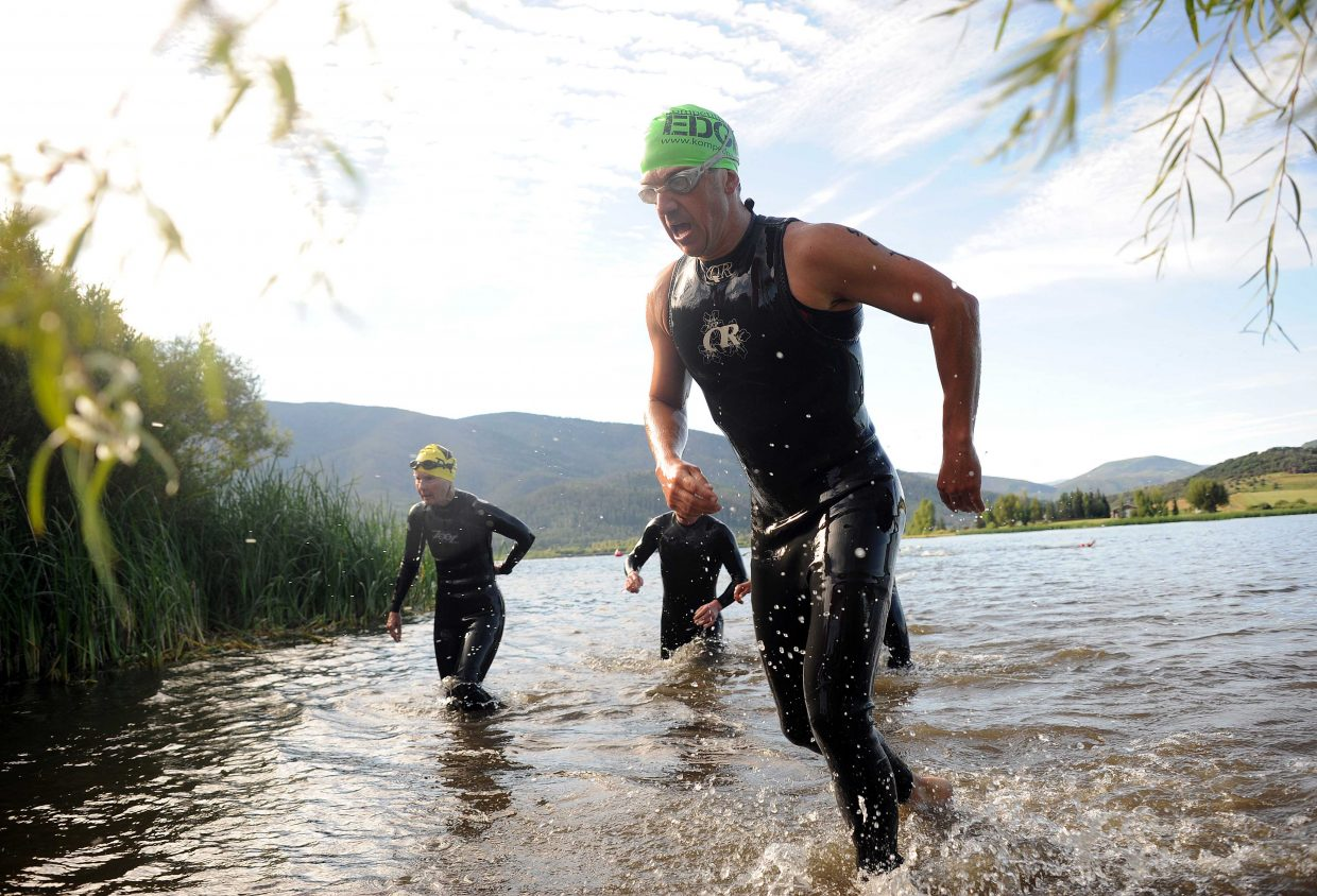Cyril Vidergar, right, rushes from the water Sunday in the Steamboat Springs Triathlon.