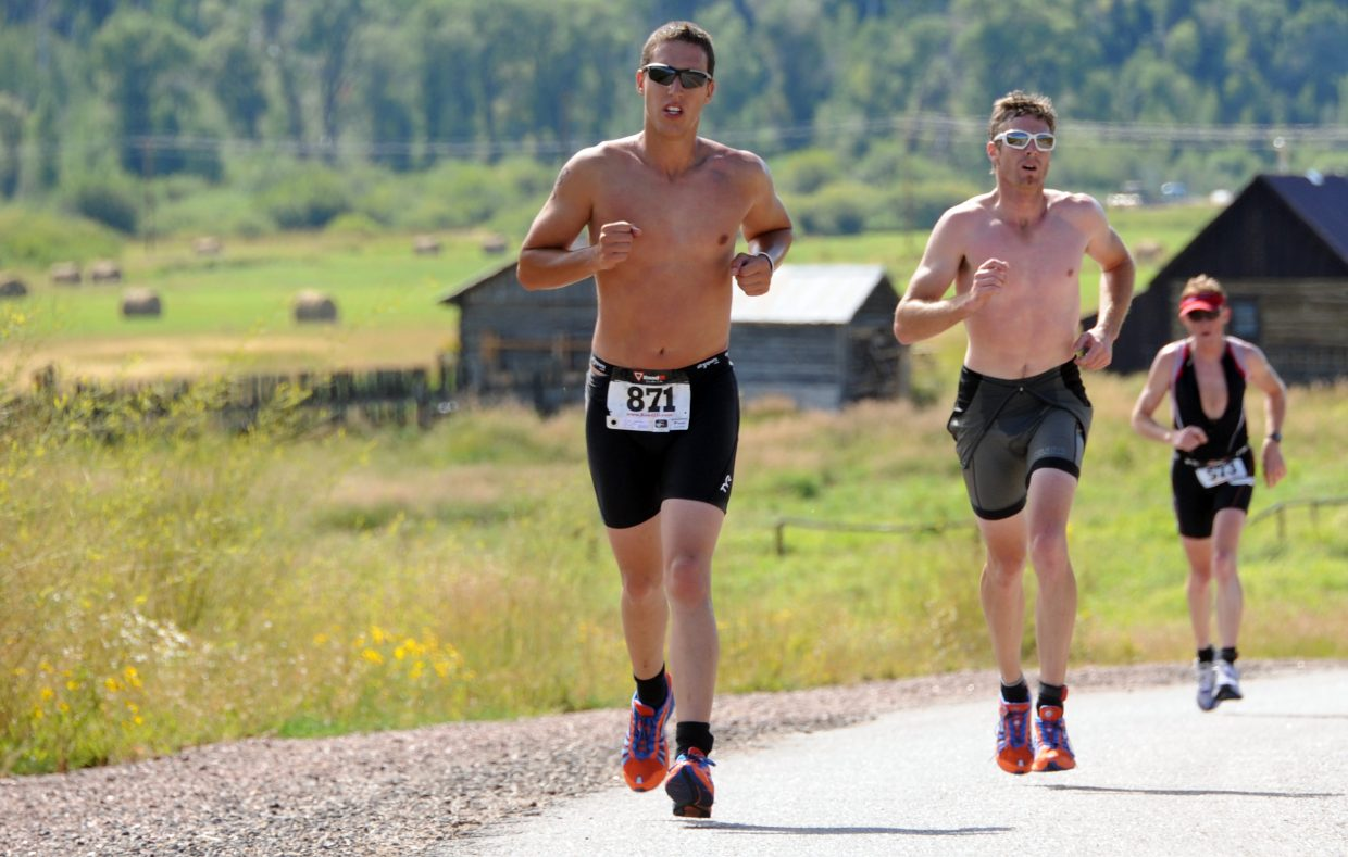 Sidney Zven, left, runs up a hill Sunday in the Steamboat Springs Triathlon.