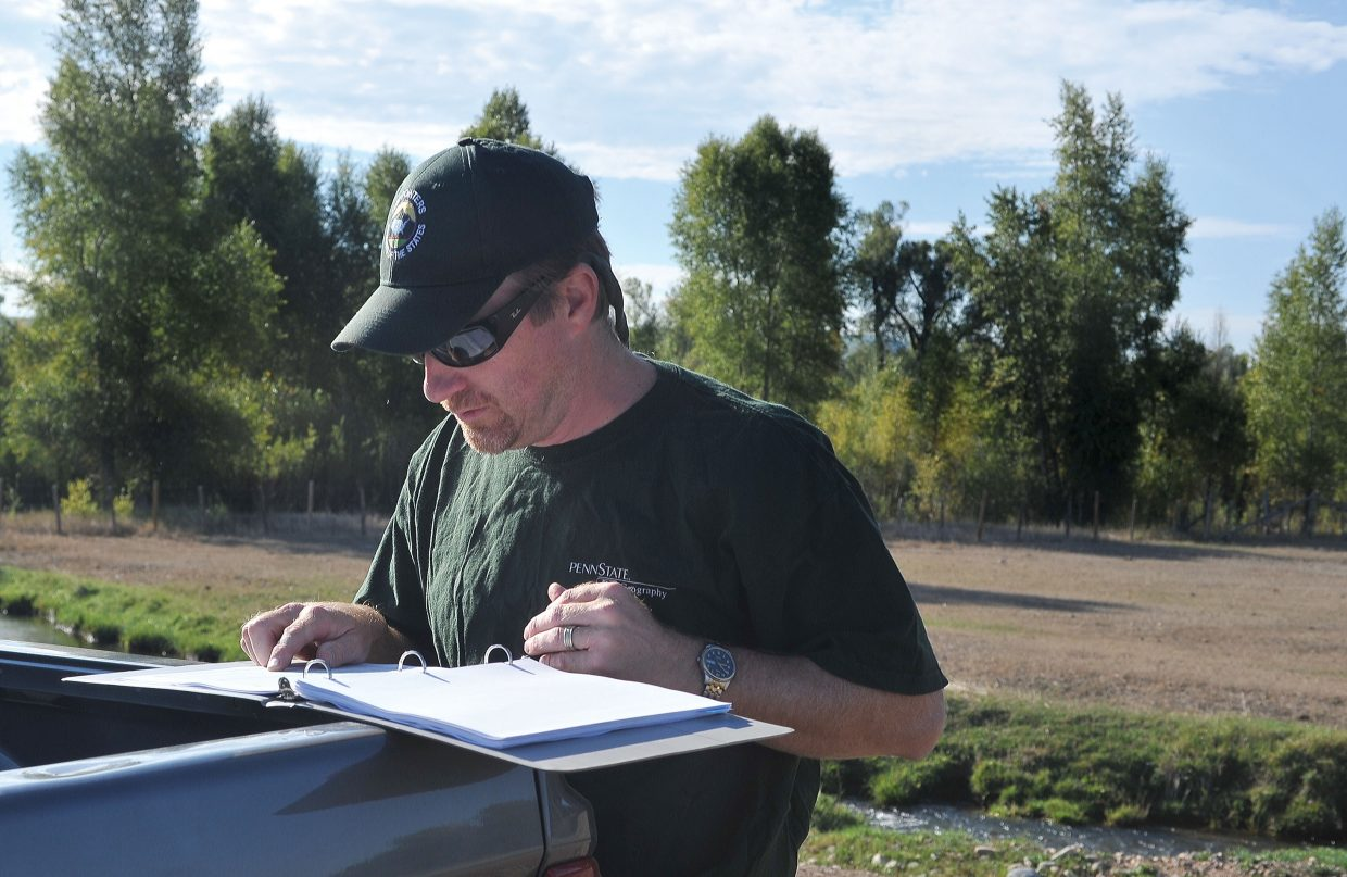 Water Commissioner Brian Romig checks some paperwork before heading to check out an irragation ditch on the lower Elk River.