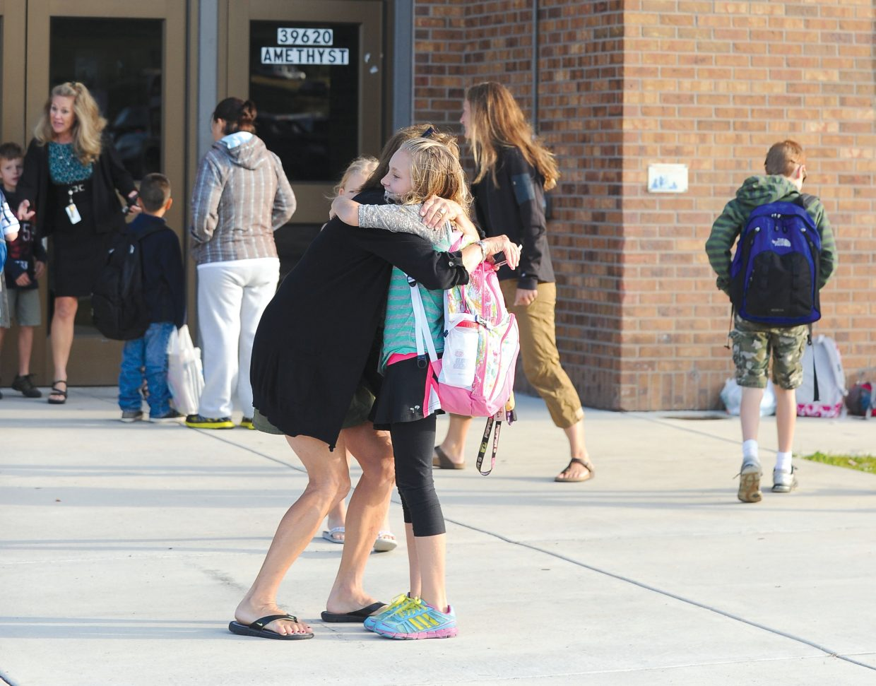 Fifth-grader Emily Schneider gets a hug from Sherry Holland on the first day of school Wednesday at Strawberry Park Elementary School.