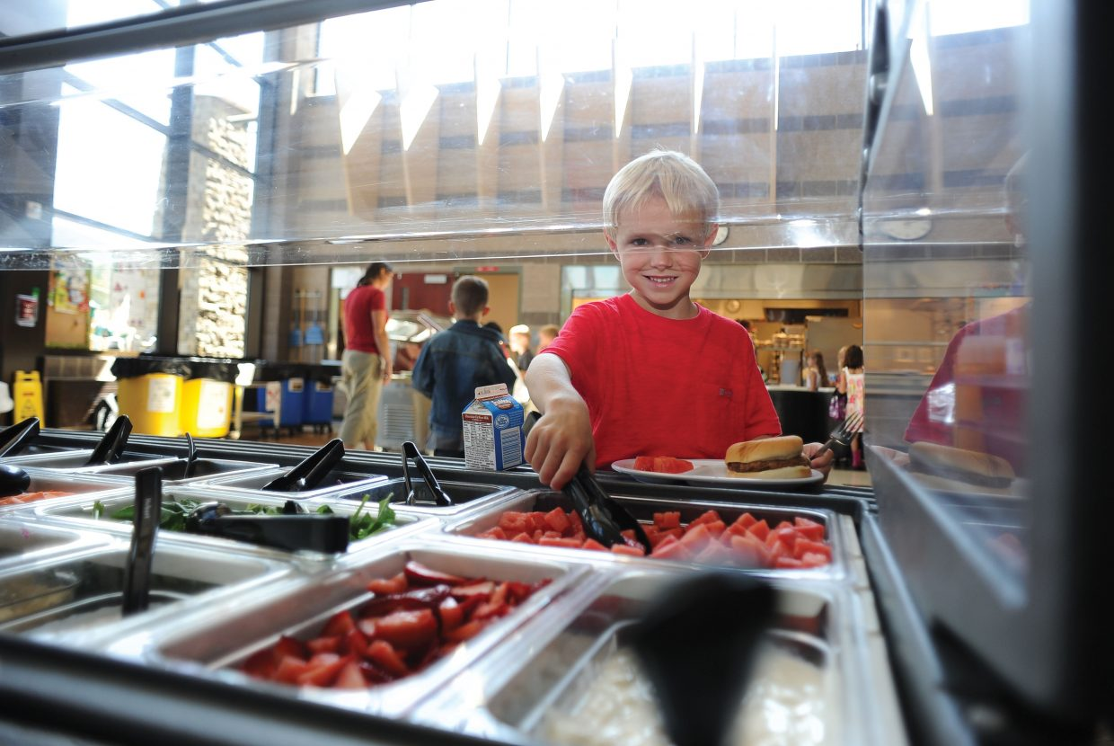 First-grader Braden Duty grabs some fruit Wednesday during the first day of classes at Soda Creek Elementary School.