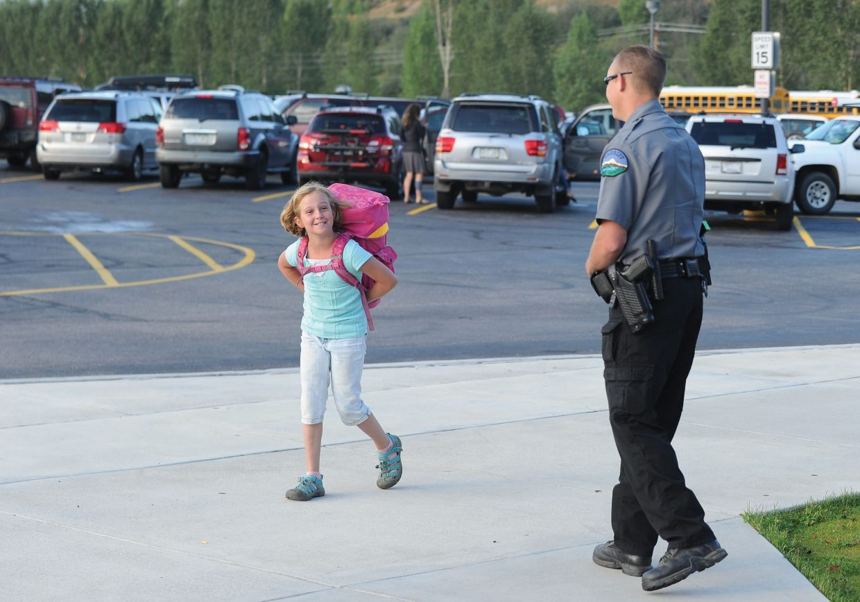 Fourth-grader Sofia Karch is greeted by Routt County Sheriff's Office Deputy Bryan Wojtkiewicz on the first day of school Wednesday at Strawberry Park Elementary School.