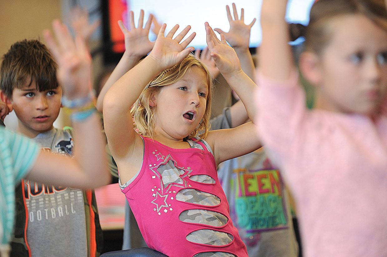 Soda Creek Elementary School fourth-grader Eliza Bodden and her classmates run through a series of exercises designed to get the blood flowing before getting to work in Cecily Townsend's class Wednesday.