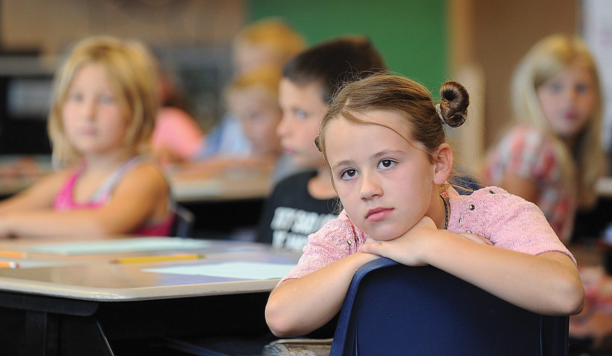 Fourth-grader Charlotte Brooks listens to teacher Cecily Townsend on Wednesday during the first day of classes at Soda Creek Elementary School.