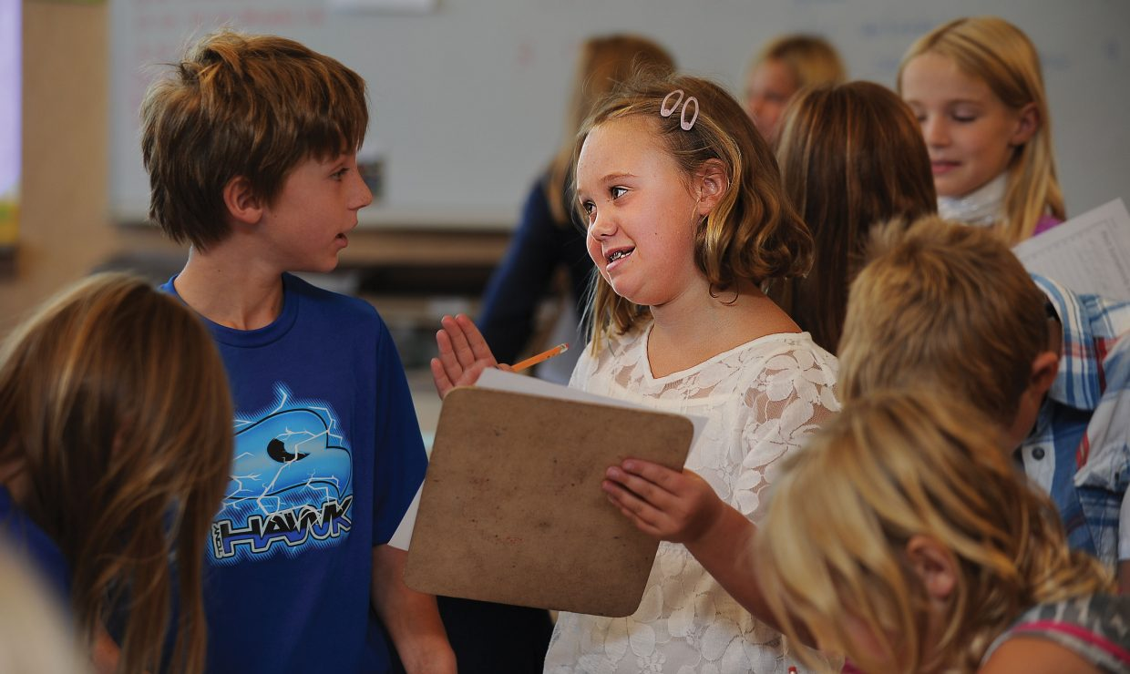 Fourth-grade student Paige Watson visits with classmates while completing an assignment in Cecily Townsend's class at Soda Creek Elementary School on Wednesday.
