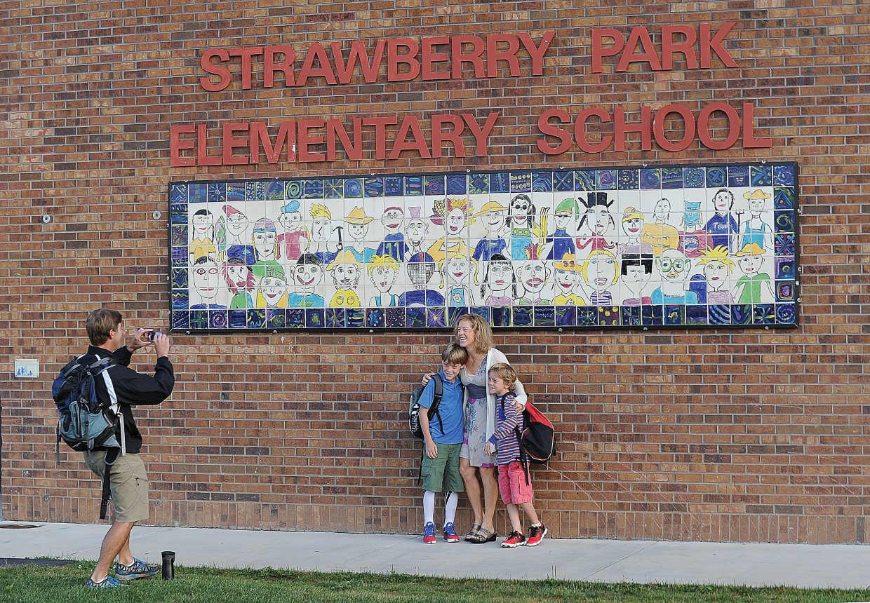 Chris Adams takes a family photo Wednesday in front of Strawberry Park Elementary School of his wife Lisa, center, with sons Kellen, who is going into fourth grade, and Braden, who is going into second grade. Chris Adams teaches physical education at the middle school, and Lisa Adams is a fourth-grade teacher at Strawberry Park.