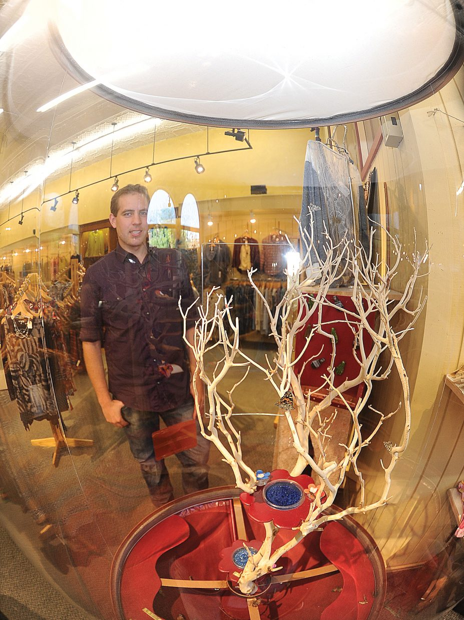 Chris Dillenbeck, who owns Chrysalis with his wife, Lindsay, stands behind a butterfly enclosure inside the downtown store.
