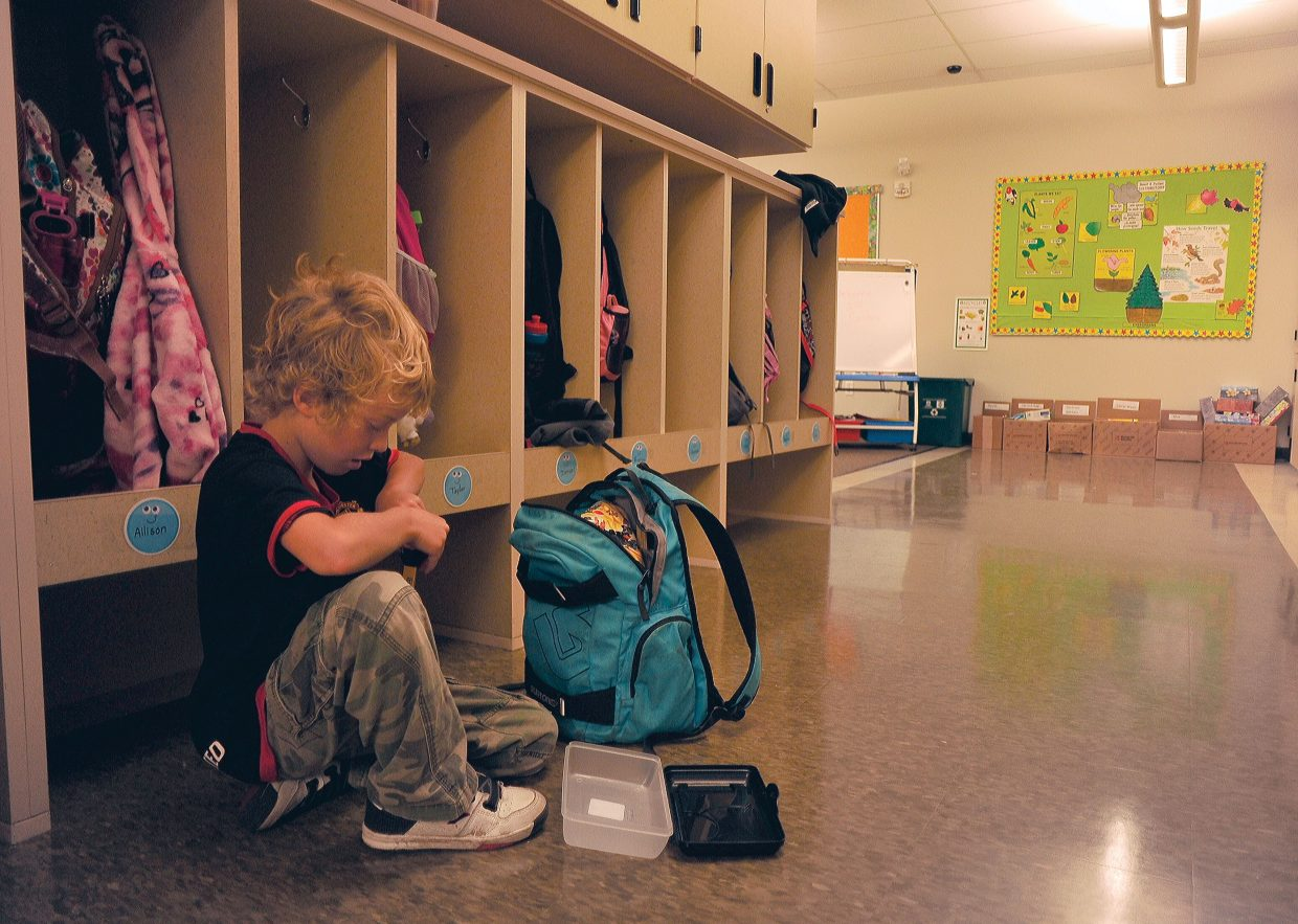 Second-grader James Appel unloads his backpack inside his Soda Creek Elementary School classroom on the first day of school Wednesday.
