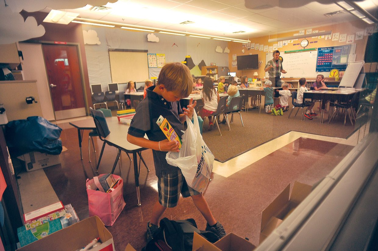 Second-grader Andrew Kempers unloads school supplies on his first day back at Soda Creek Elementary School on Wednesday. Children at Soda Creek, Strawberry Park and the high school all returned to classes Wednesday.