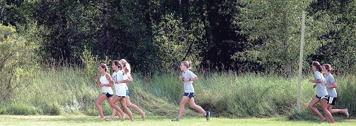 Members of the Steamboat Springs High School girls cross-country team complete a lap around Emerald Park this week during training.