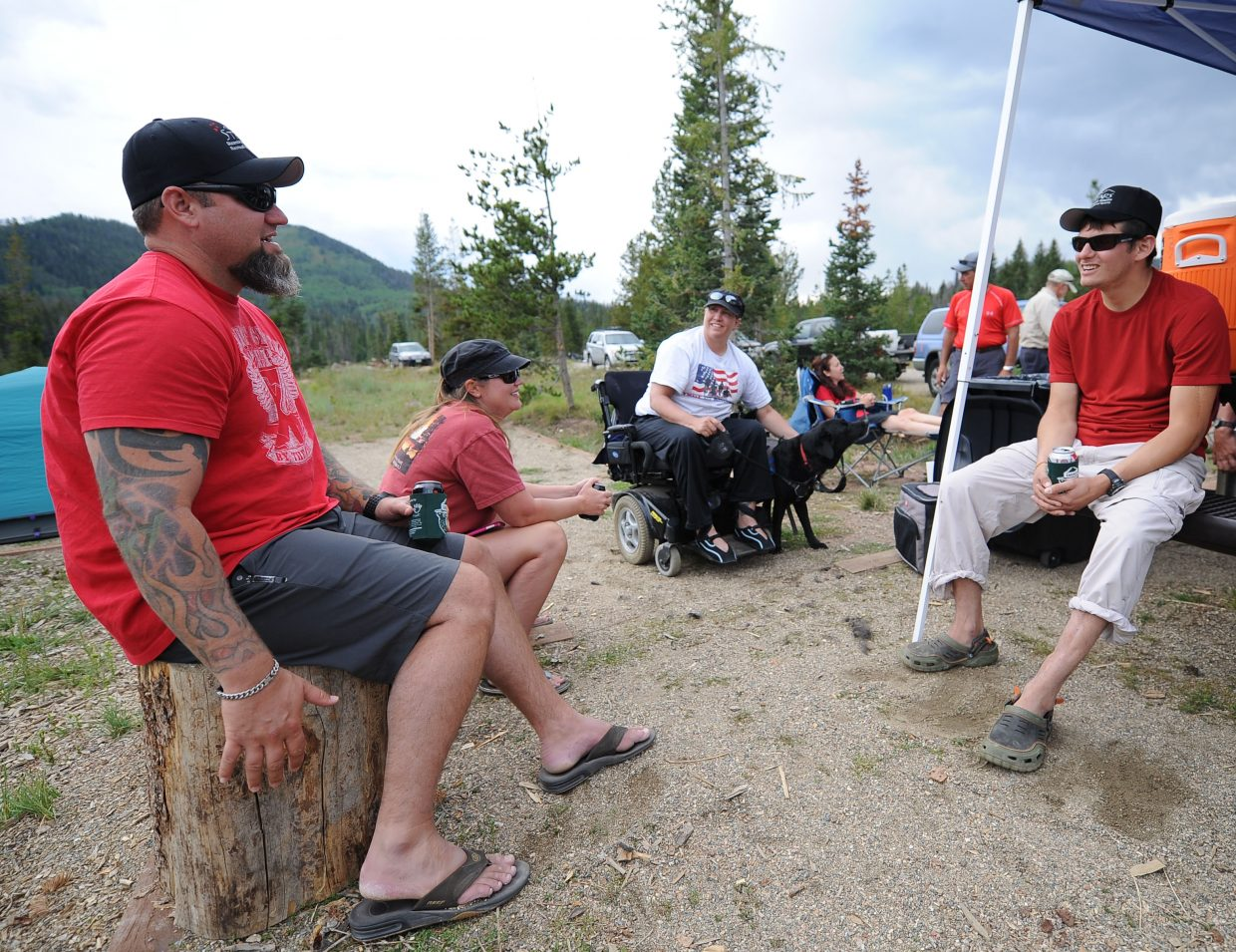 Wade Sharbono, from left, Diana Sharbono, Kerry Conway and Aaron Bugg share stories while the fire warms up during the STARS and Stripes Heroes Camp at Hahn's Peak Lake last month near Steamboat Springs. The camp drew about a dozen veterans to the area for camping, water skiing and simply relaxing.