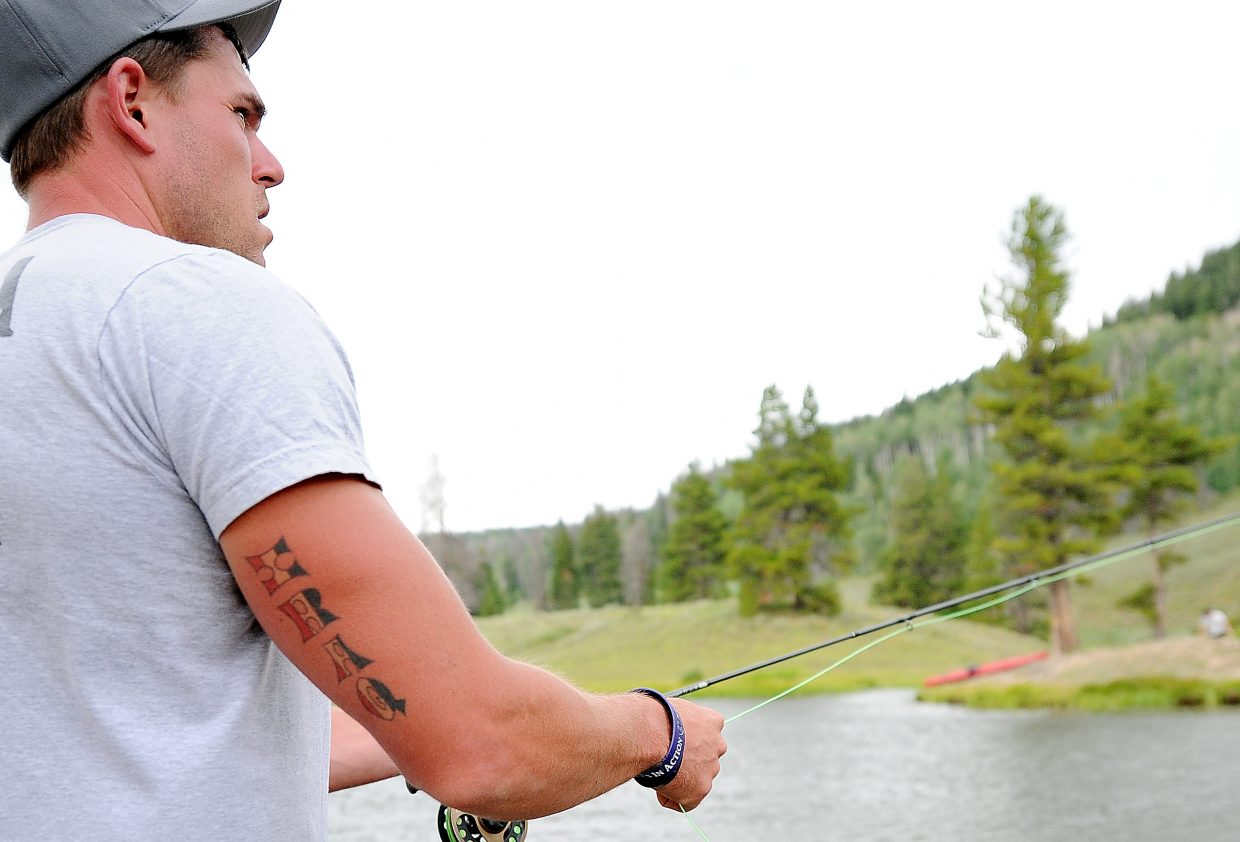 Josh Rynders casts into Hahn's Peak Lake. Rynders had hoped to make a career out of the Marine Corps, but that all changed when a mortar round landed near him and cut into his legs and body. He said that recovering from such an injury is a long, hard process but that being able to spend time with fellow veterans who have gone through the same process is helpful.