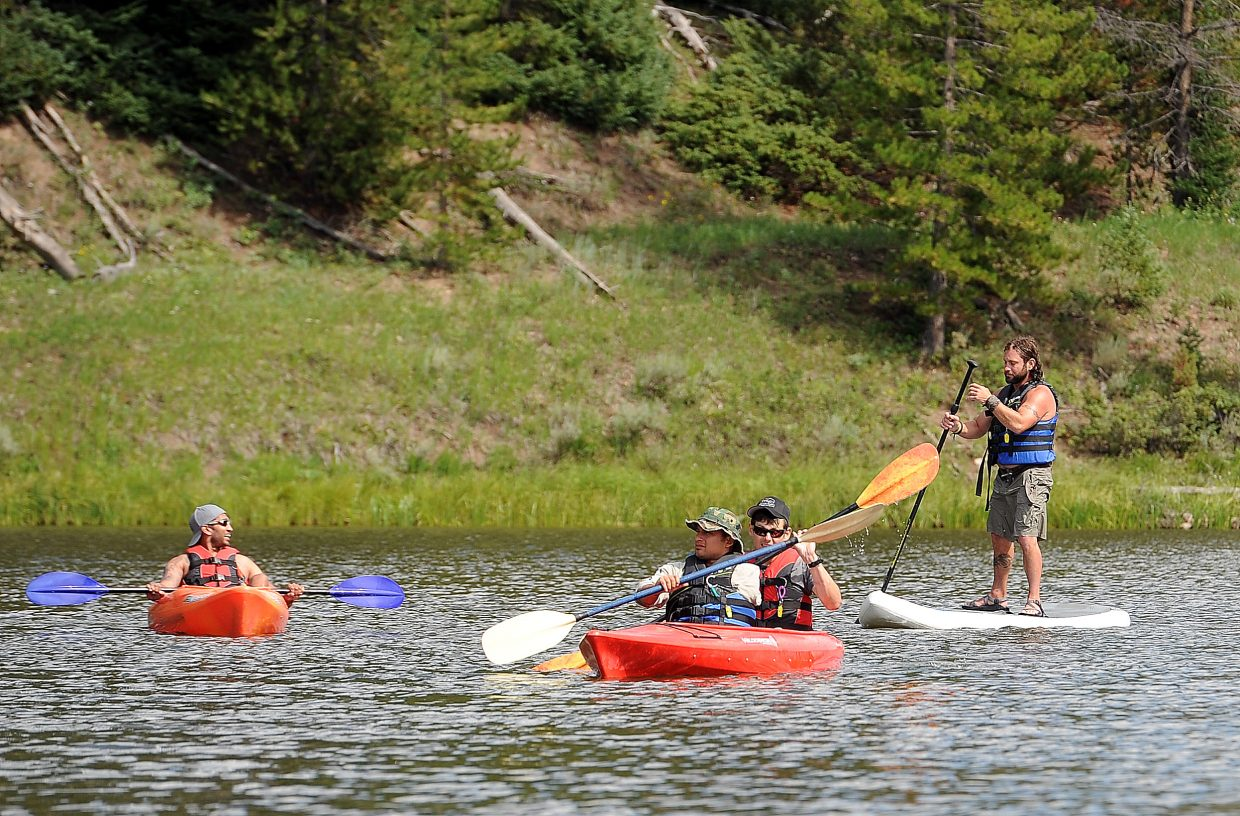 Chris Chatwin, from left, Dan Acosta, Aaron Bugg and Calder Young share a moment on the water of Hahn's Peak Lake north of Steamboat Springs. Chatwin, Acosta and Bugg attended the camp as wounded veterans, and Young, who also falls into that category, was volunteering. The men said the experience goes far beyond enjoying a vacation — it offers them the chance to connect with others going through some of the same things they are.