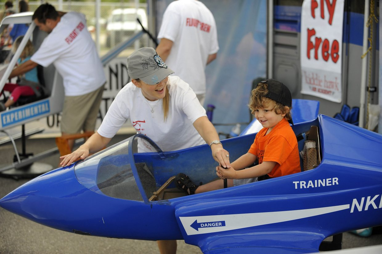 Sharon Lips helps George Boisjoli, 3, fly a trainer at the Kiddie Hawk Air Academy at the Wild West Air Fest on Saturday.