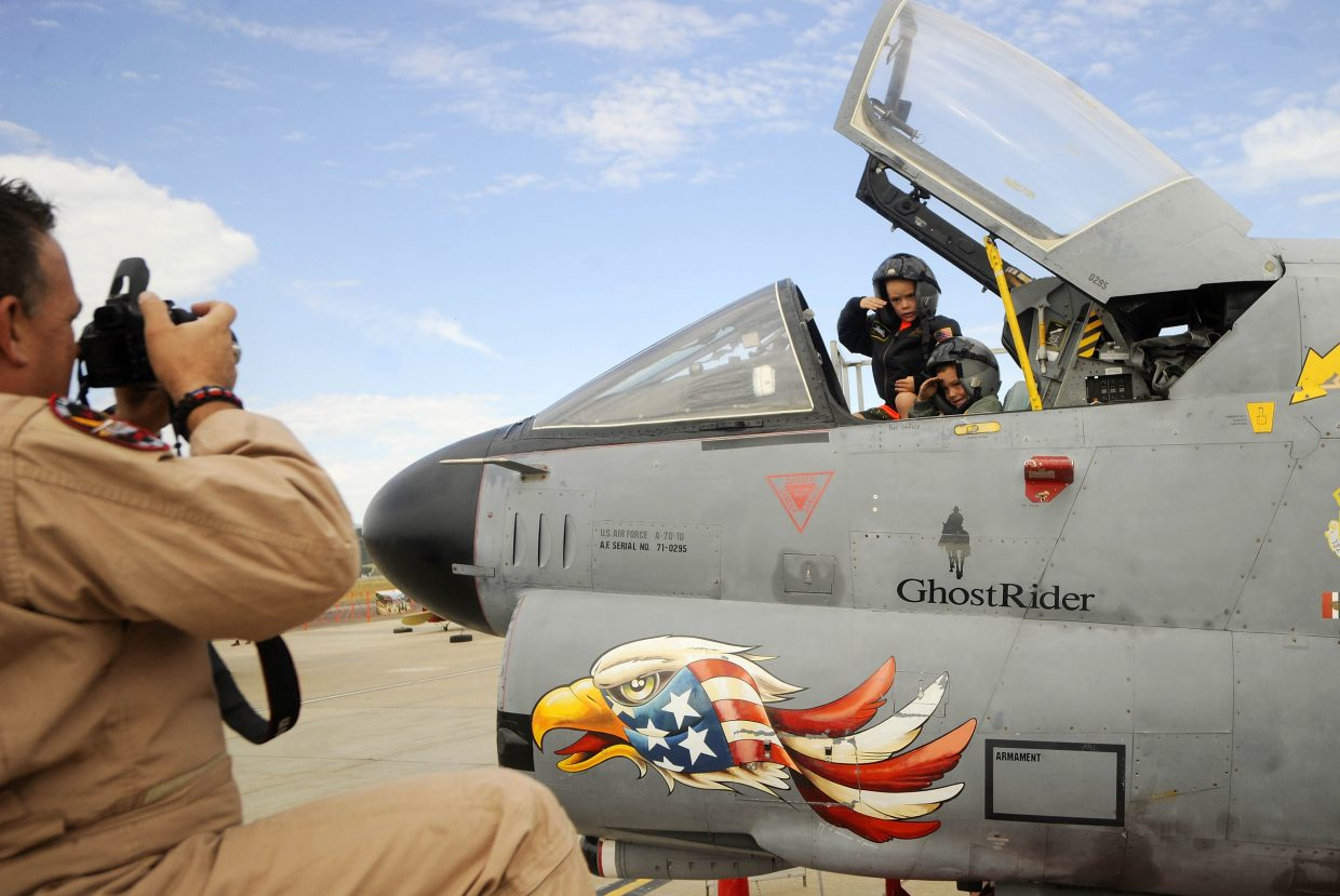 Frank Alexander, 6, right, and his brother Ike, 5, salute as Dewey Larson takes their picture inside the cockpit of a A-7 Corsair II on Saturday during the Wild West Air Fest at Steamboat Springs Airport.
