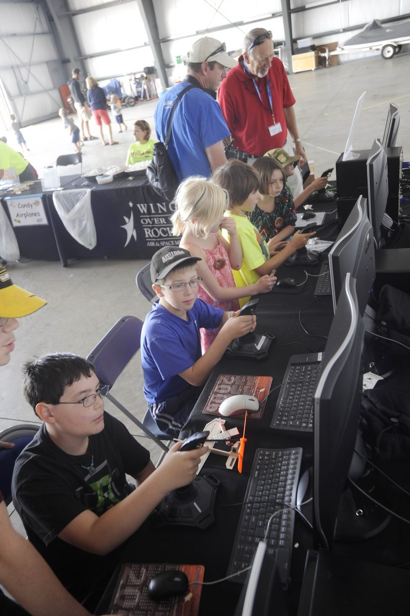 Children use flight simulators in the Wings Over the Rockies Air & Space Museum exhibit Saturday during the Wild West Air Fest at Steamboat Springs Airport.