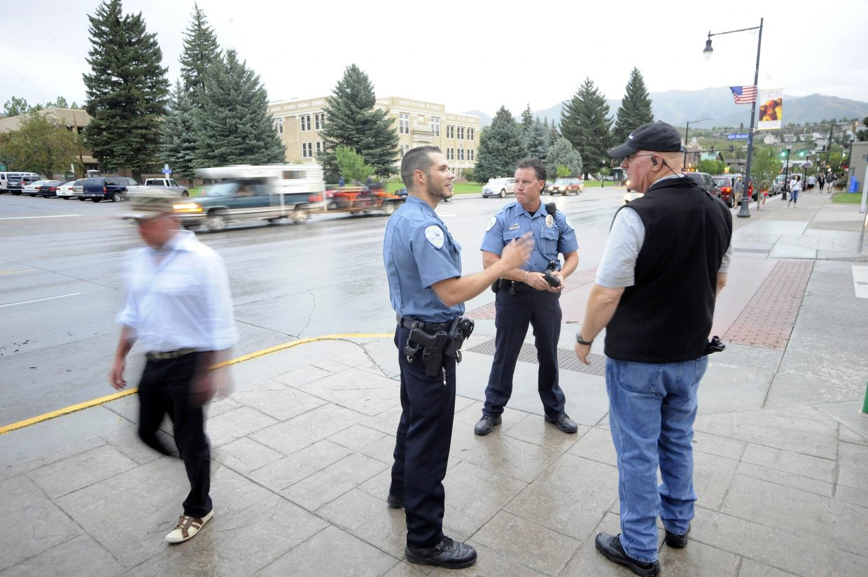 Steamboat Springs Police Department officer Kiel Petkoff talks with police chaplain Dave McKnight, right, and officer Nick Bosick on Friday night at Sixth Street and Lincoln Avenue.