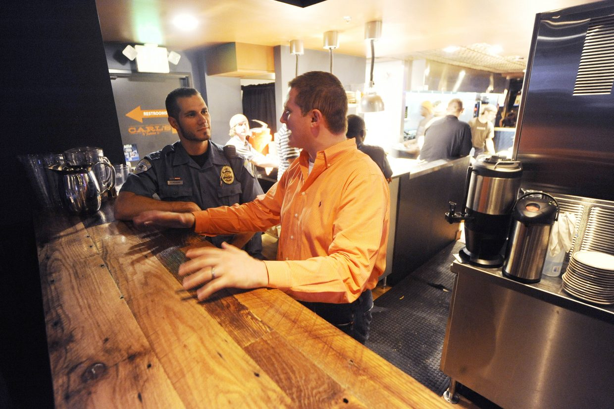 Steamboat Springs Police Department officer Kiel Petkoff checks in with Carl's Tavern co-owner Collin Kelley on Friday night.