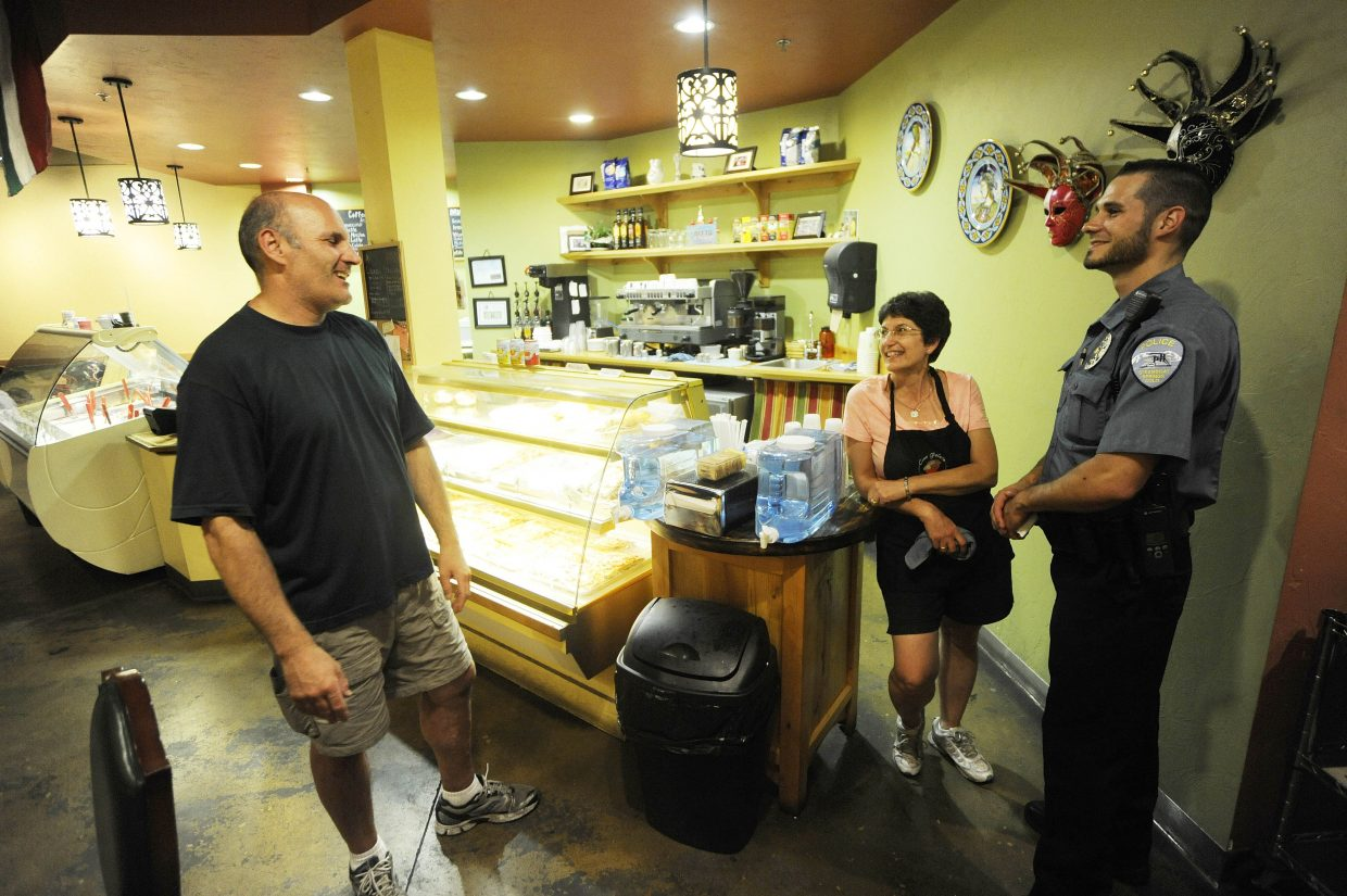 Steamboat Springs Police Department officer Kiel Petkoff checks in with Ciao Gelato owners Massimo Erspamer and Lynne Romeo on Friday night.