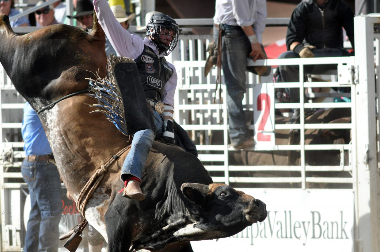 A cowboy hangs on during the Rocky Mountain Bull Bash on Sunday.