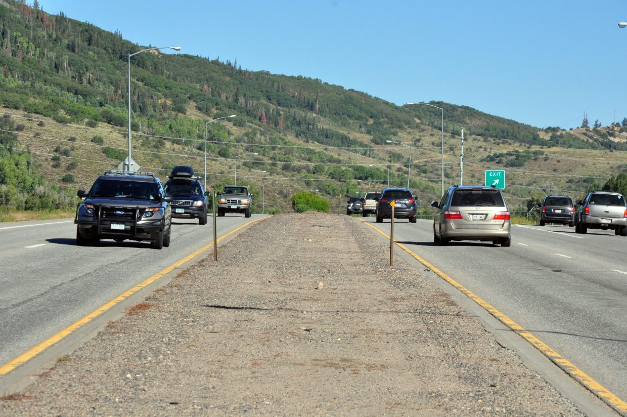 Cars cruise by the current medians on U.S. HIghway 40 near the southern entrance of Steamboat Springs. Work to improve the medians with landscaping starts Tuesday.