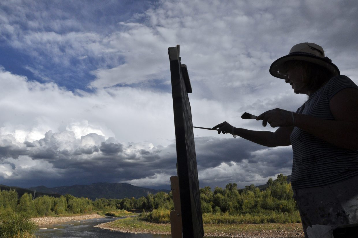 Carol Jean paints a scene of the Yampa River as storm clouds form over Mount Werner on Wednesday evening.