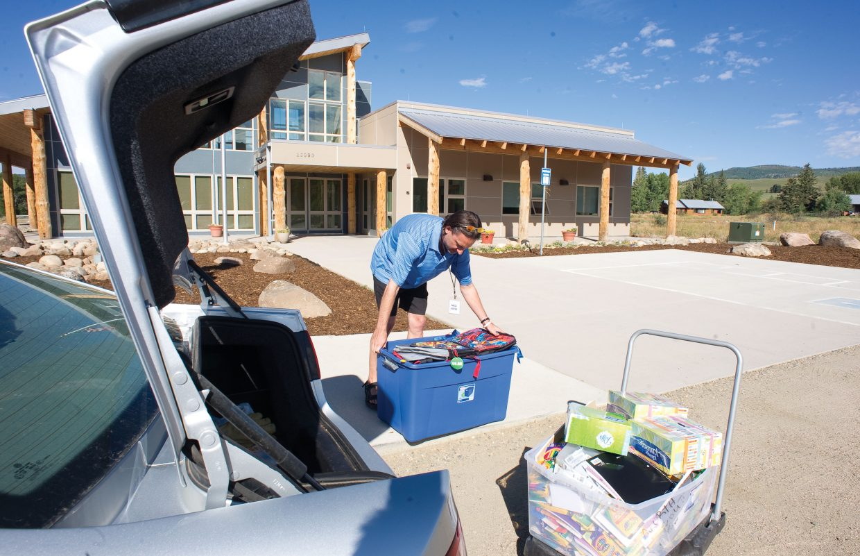George Avgares, with Colorado Student Care, delivers a tub filled with school supplies and another filled with backpacks to the North Routt Community Charter School on Thursday.