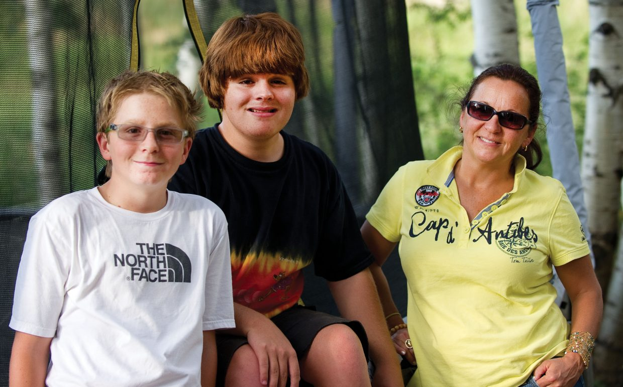 James Dickson, middle, poses for a family photo on the edge of his trampoline with his brother Louis, left, and Babette, his mom.