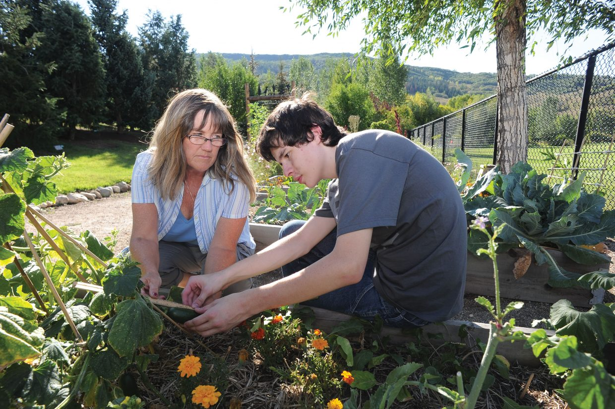 Horticultural Therapist Deb Reed works with Evan Duran at the Yampa River Botanic Park as part of Community Cultivation. Community Cultivation, a program of the Yampa Valley Autism Program, is a horticulture program for youths with disabilities or a part of at-risk populations.