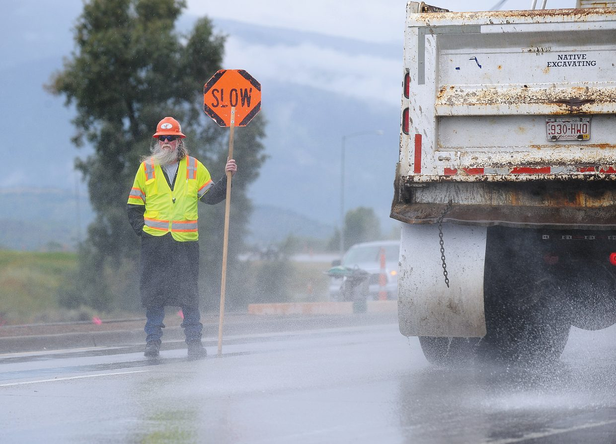 Don Fickle, of CC Enterprises, directs traffic in the rain Monday morning along U.S. Highway 40 south of Steamboat Springs. Crews from Native Excavating were working on improvements to the medians despite the rain.