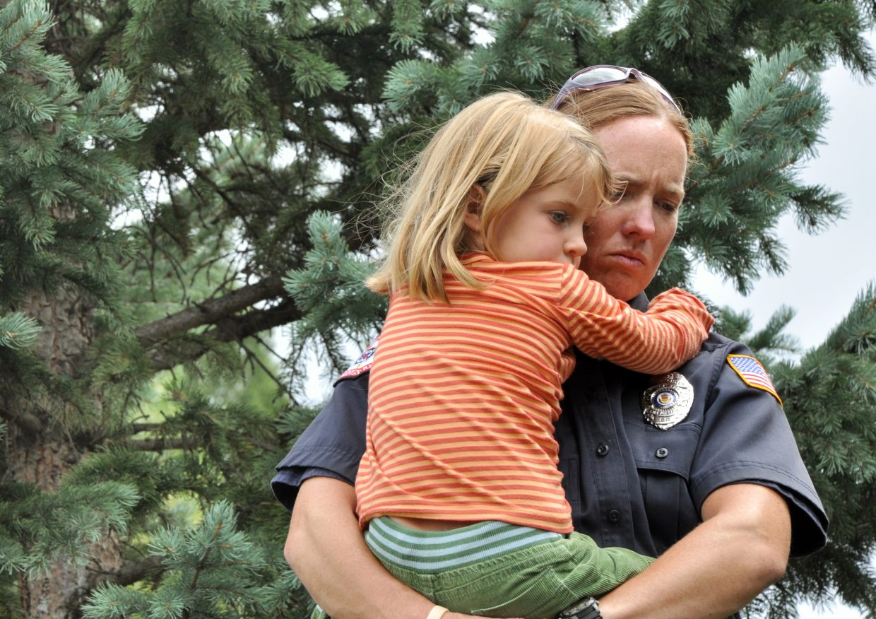 Steamboat Springs firefighter Marnie Smith holds Adelyn Armstrong during a Sept. 11 reflection ceremony at the Yampa River Botanic Park. More than 50 community members gathered to mark the 10th anniversary of the Sept. 11, 2001, terrorist attacks.