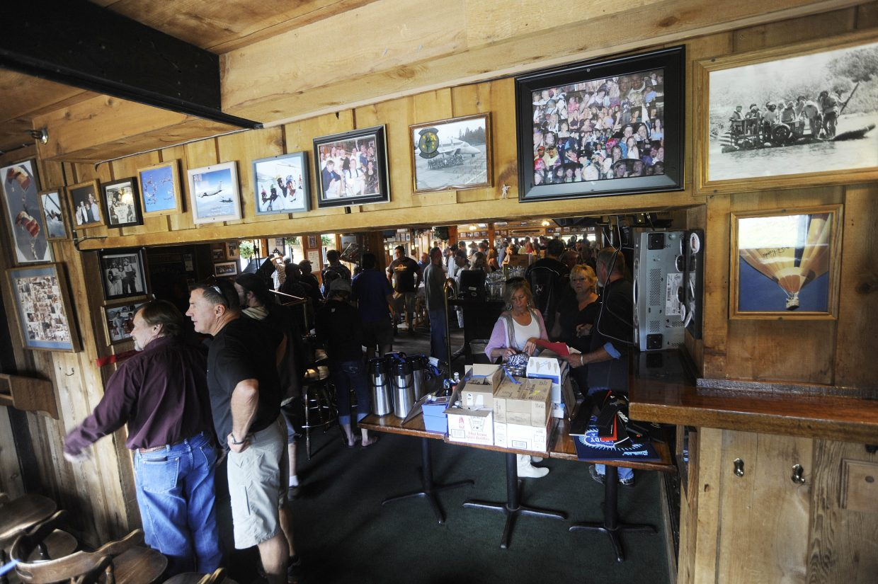 People browse the memorabilia and photos on the wall during Wednesday's auction at The Tugboat Grill & Pub.