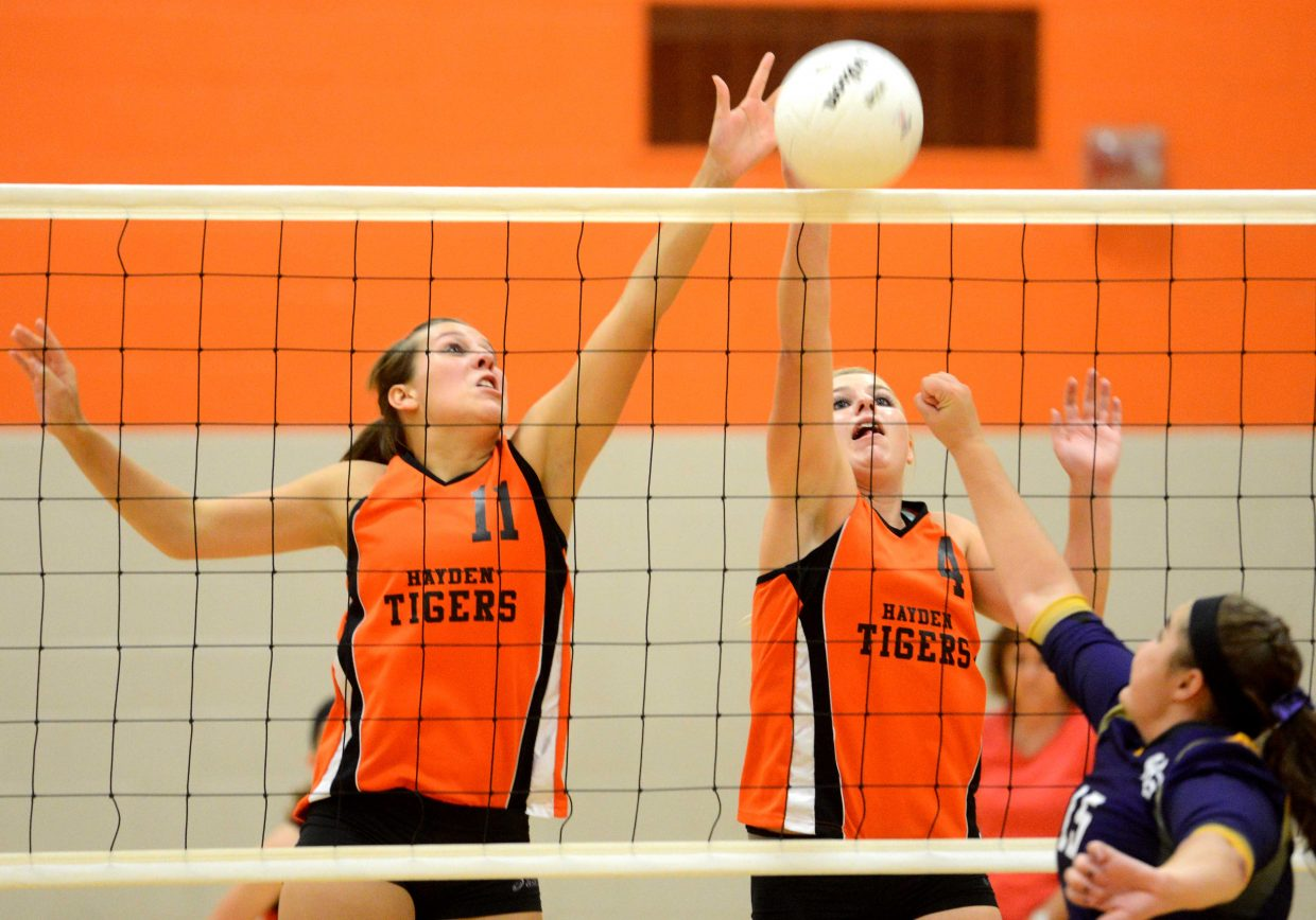 Hayden's Chancey Graham, left, and Jordan Temple tip a ball over the net Thursday against West Grand.