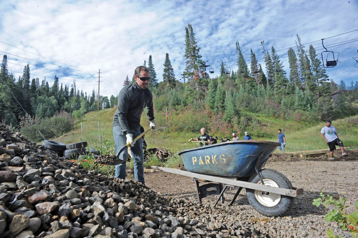 SmartWool employee Blair Labaree loads rocks into a wheelbarrow near the bottom of the Alpine slide at Howelsen Hill on Thursday morning while replacing the deck and a wooden walkway as part of a community service project. Chad Bowdre, with the Steamboat Springs Winter Sports Club, said SmartWool employees have helped out Howelsen Hill and the Winter Sports Club as part of Servapalooza. The event is a tradition for SmartWool employees who go out into the community to complete service projects and support local organizations.