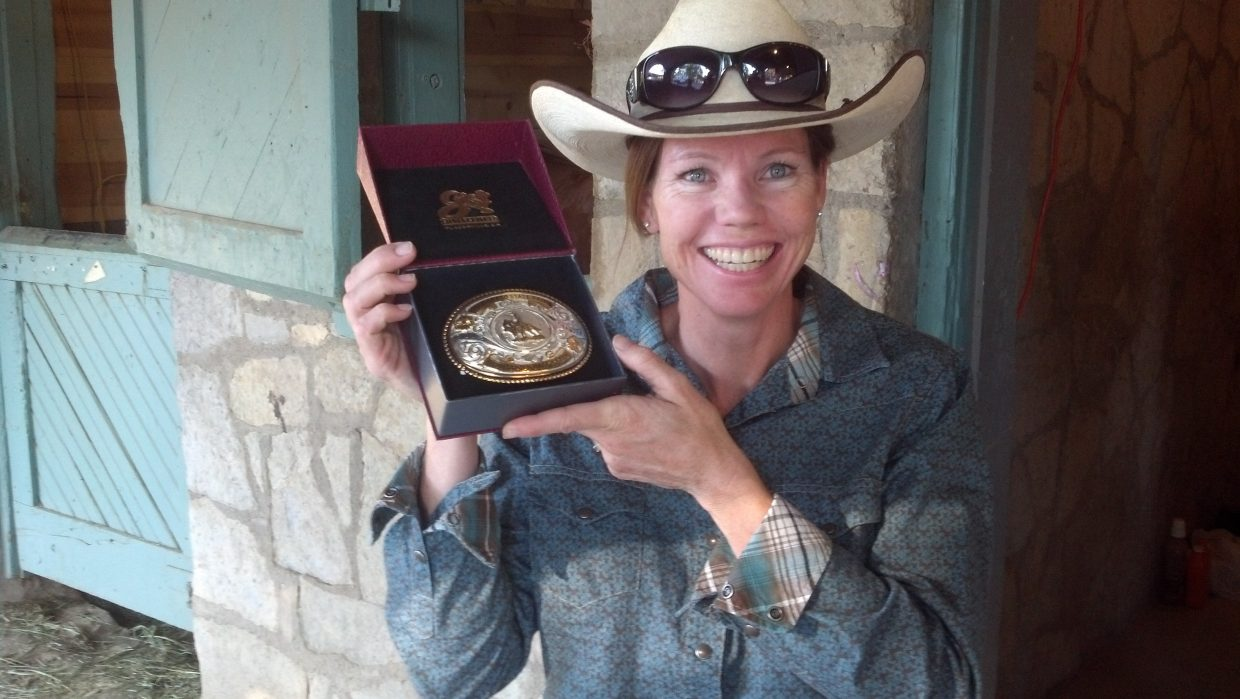 Brandy Patrick shows off one of the buckles she won in her two horse show victories at the Colorado State Fair during Labor Day weekend. Patrick competed with her husband, Jason, against some stiff competition in Pueblo.