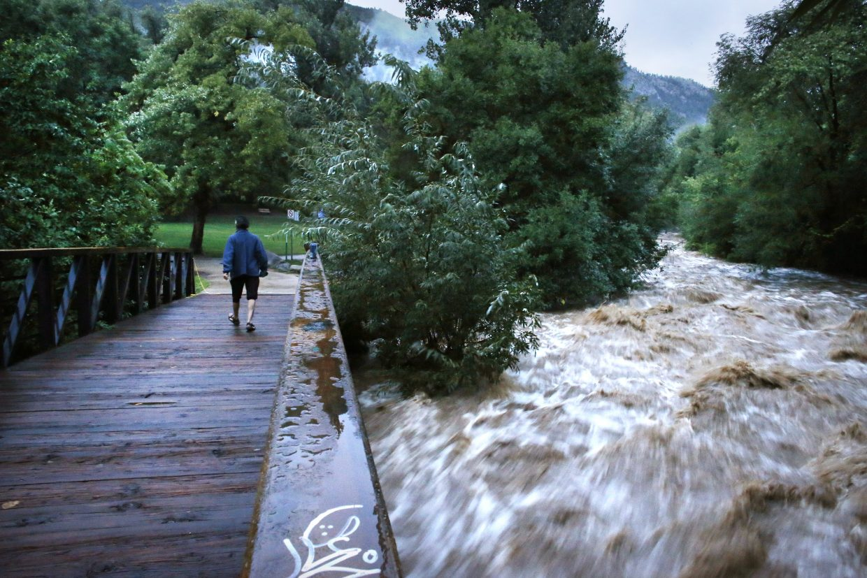 During a break in the rain Friday in Boulder, a woman walks along a footbridge over Boulder Creek near the University of Colorado campus. The creek was flowing at 5,260 cubic feet per second at noon Friday, according to the U.S. Geological Survey. The previous record for the date was 144 cfs recorded in 1993.