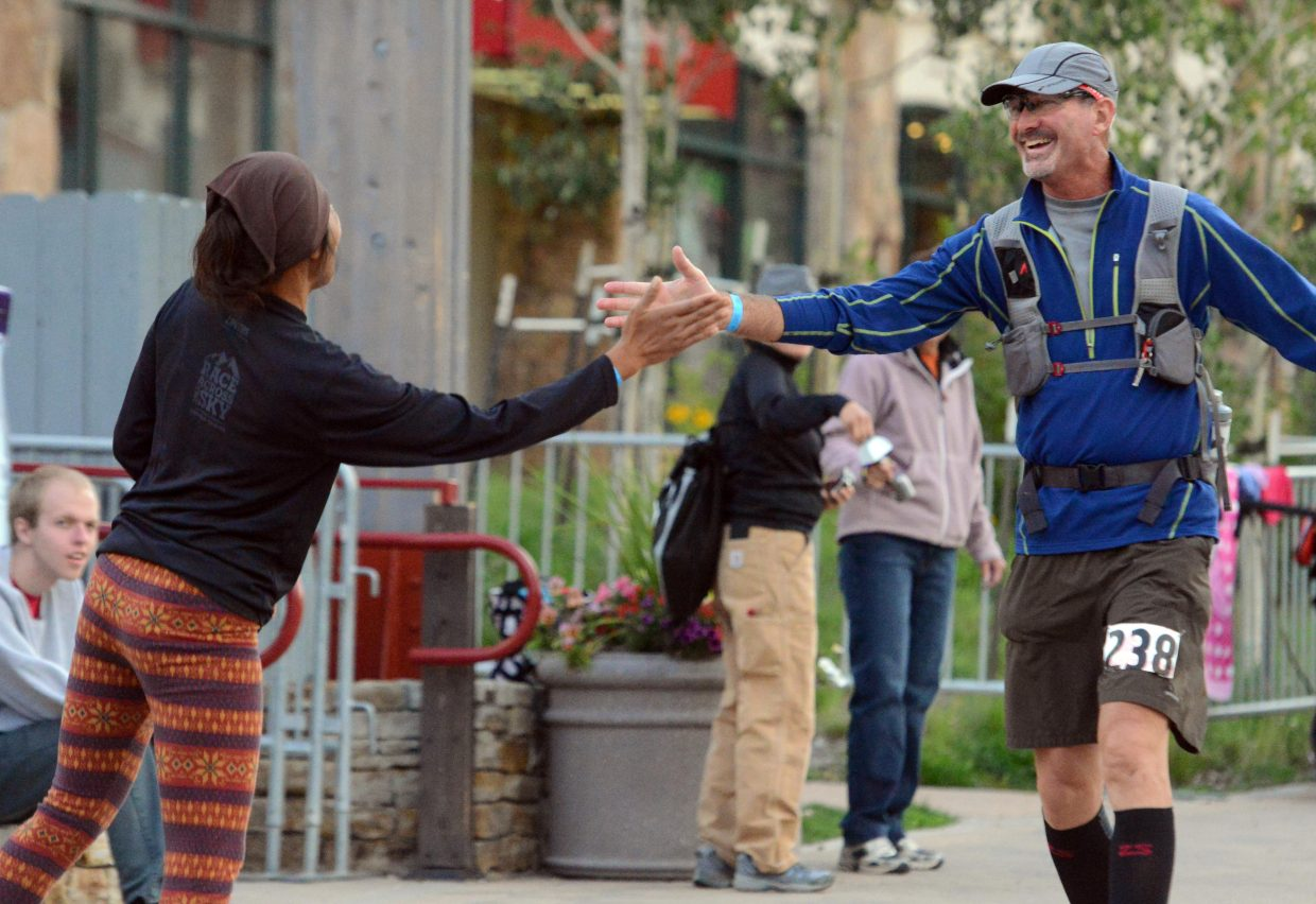 Brian Holthausen exchanges a high five as he finishes the 100-mile Run, Rabbit Run trail ultramarathon in Steamboat Springs on Saturday evening. Every racer, fast or slow, was greeted by a loud ovation as they finally reached the end of their long journey.