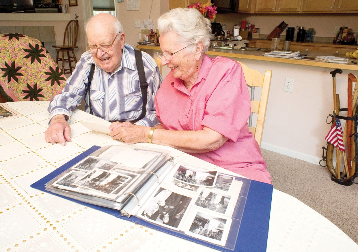 Betty Kemry, right, and Lewis, her husband of 60 years, share a laugh while looking through their wedding photos.