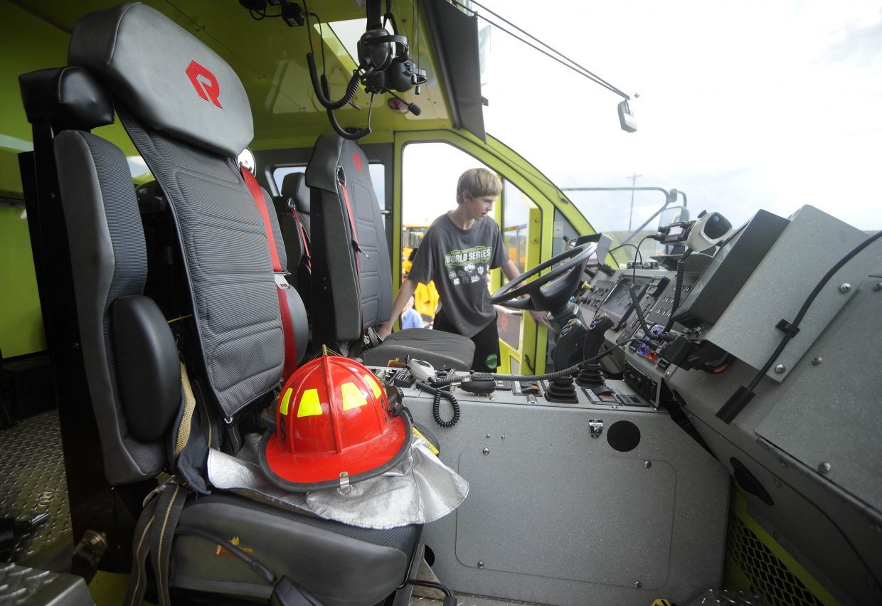Steamboat Springs 13-year-old Zach Cooke explores a fire engine during a tour of Yampa Valley Regional Airport.